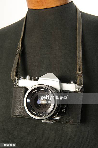 old reflex camera hanging on a mannequin