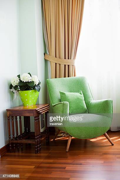Old retro green colored armchair in a vintage home interior
