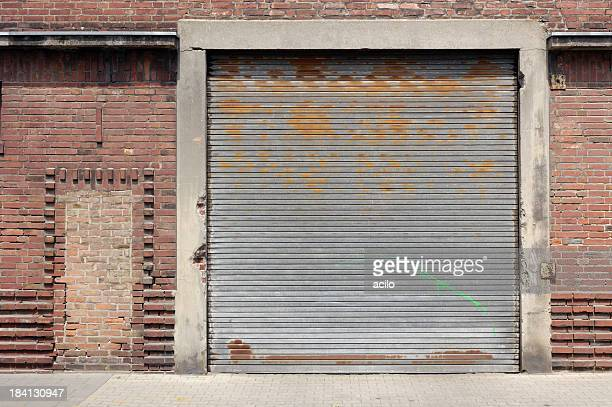 old rolling garage door and brick wall - industrial door stock pictures, royalty-free photos & images