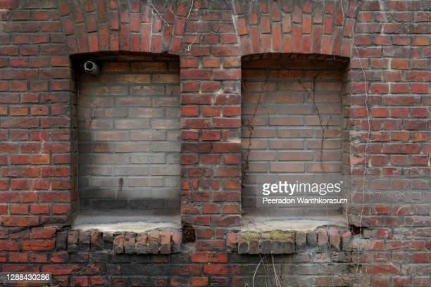 old rough dirty brick wall facade with vintage detail of rectangular windows frame filled with brick. - casa di mattoni foto e immagini stock