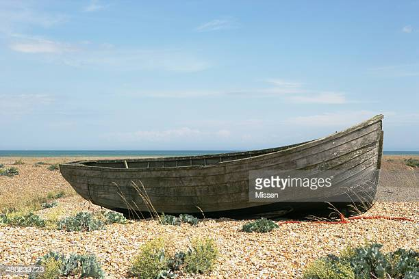 Old rowing boat on pebble beach, Dungeness, Kent, England, UK