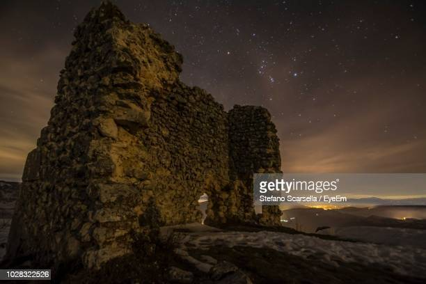 old ruin against star field at night - oude ruïne stockfoto's en -beelden