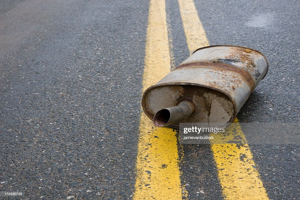 Old rusted muffler laying in the center of the road : Stock Photo