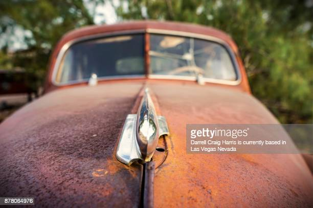 old rusty car (hood ornament in foreground) in the nevada desert - hood ornament stock pictures, royalty-free photos & images
