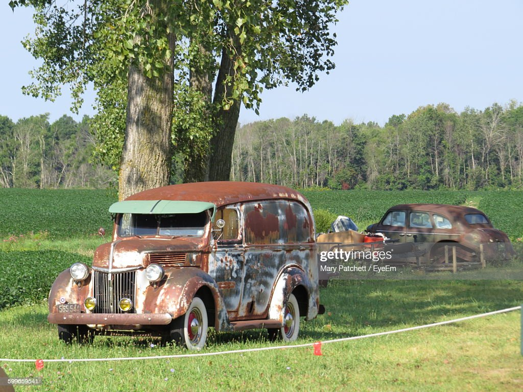 Old Rusty Cars On Grassy Field Against Clear Sky Stock Photo ...