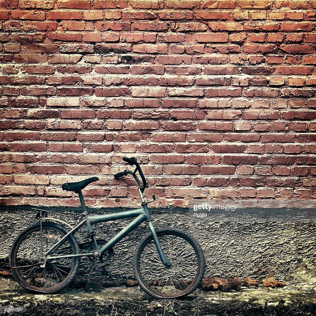 Old rusty vintage bicycle leaning against a brick wall : Stock Photo