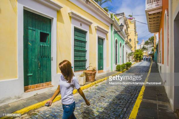 old san juan, woman walking in a street - old san juan stock pictures, royalty-free photos & images