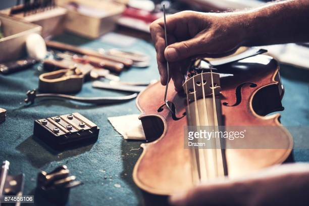 old school repairman looking into violin's soul - instrument maker stock photos and pictures