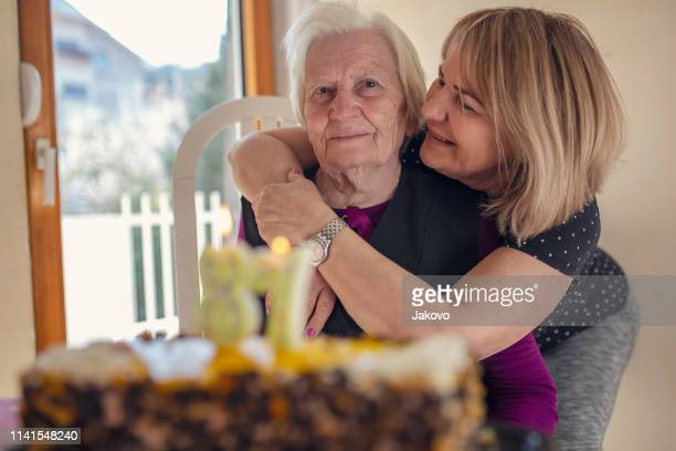 old senior woman celebrating her 87th birthday with her loved ones - great grandmother stock pictures, royalty-free photos & images