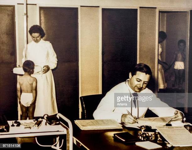 Old sepia archival photograph showing doctor and nurse examining school children in their underwear at dispensary in the 1950s
