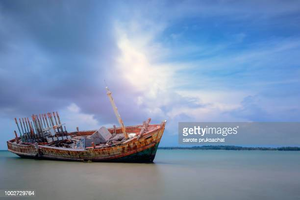 old shipwreck boat abandoned stand on beach with blue sky . - sunken stock pictures, royalty-free photos & images