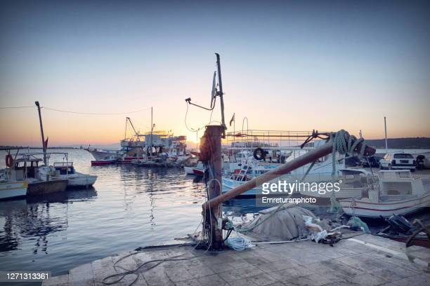 old shipyard crane and anchored boats at ildir marina at sunset. - emreturanphoto stock pictures, royalty-free photos & images