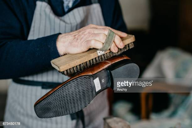 old shoemaker is polishing a shoe - calzature di pelle foto e immagini stock