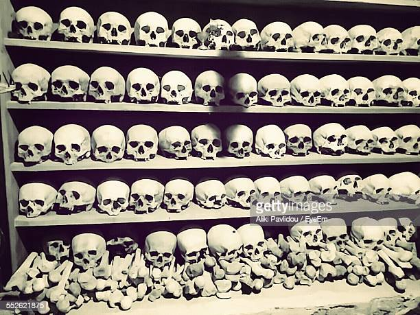 old skulls and bones placed on shelves - crypt stock photos and pictures