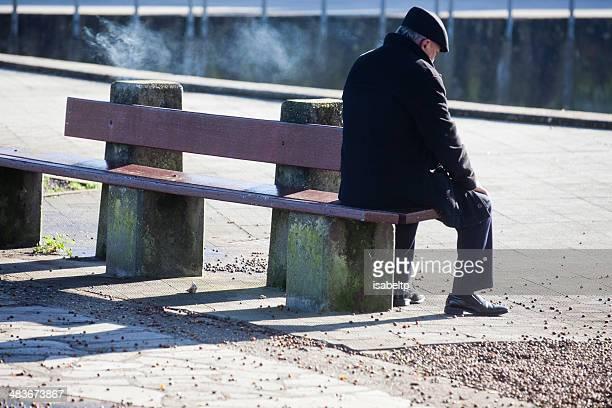 velho fumar homem em um banco - só um homem idoso - fotografias e filmes do acervo