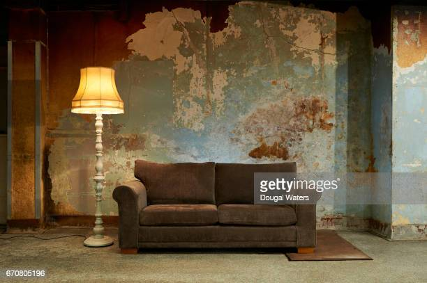 old sofa and vintage floor lamp in decaying room. - decline stock pictures, royalty-free photos & images