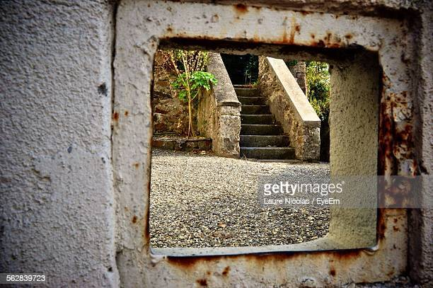 Old Staircase Seen Through Rusty Window Frame