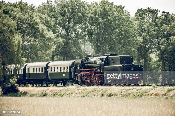 Old steam train pulling railway cars driving through the countryside