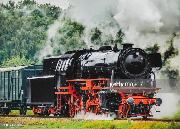"old steam train with a lot of smoke coming from the chimney driving through the countryside. - ""sjoerd van der wal"" or ""sjo"" stock pictures, royalty-free photos & images"