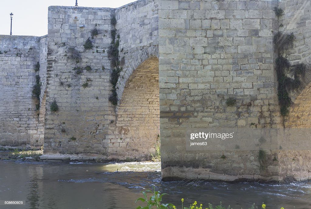 Old stone bridge block with arches and water : Stock Photo