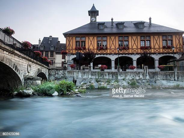 Old stone bridge over a large river and City Hall, in the village of Arreau, France