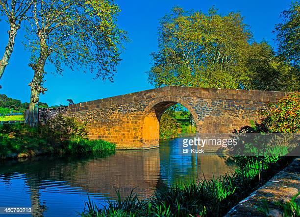 Old stone bridge spans the Canal du Midi
