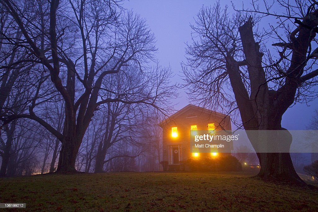 Old stone house on foggy night : Stock Photo