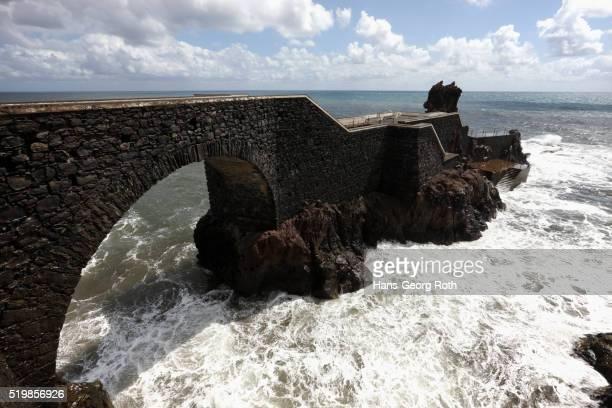 Old stone jetty bridge near Ponta do Sol in Portugal