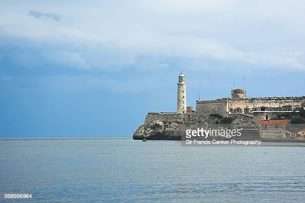 Old stone lighthouse and El Morro castle as seen from Havana's Malecon, Cuba