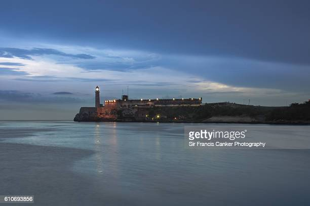 Old stone lighthouse and El Morro castle illuminated at dusk in Havana, Cuba