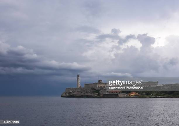 Old stone lighthouse and El Morro castle seen from Havana's Malecon before the storm, Cuba