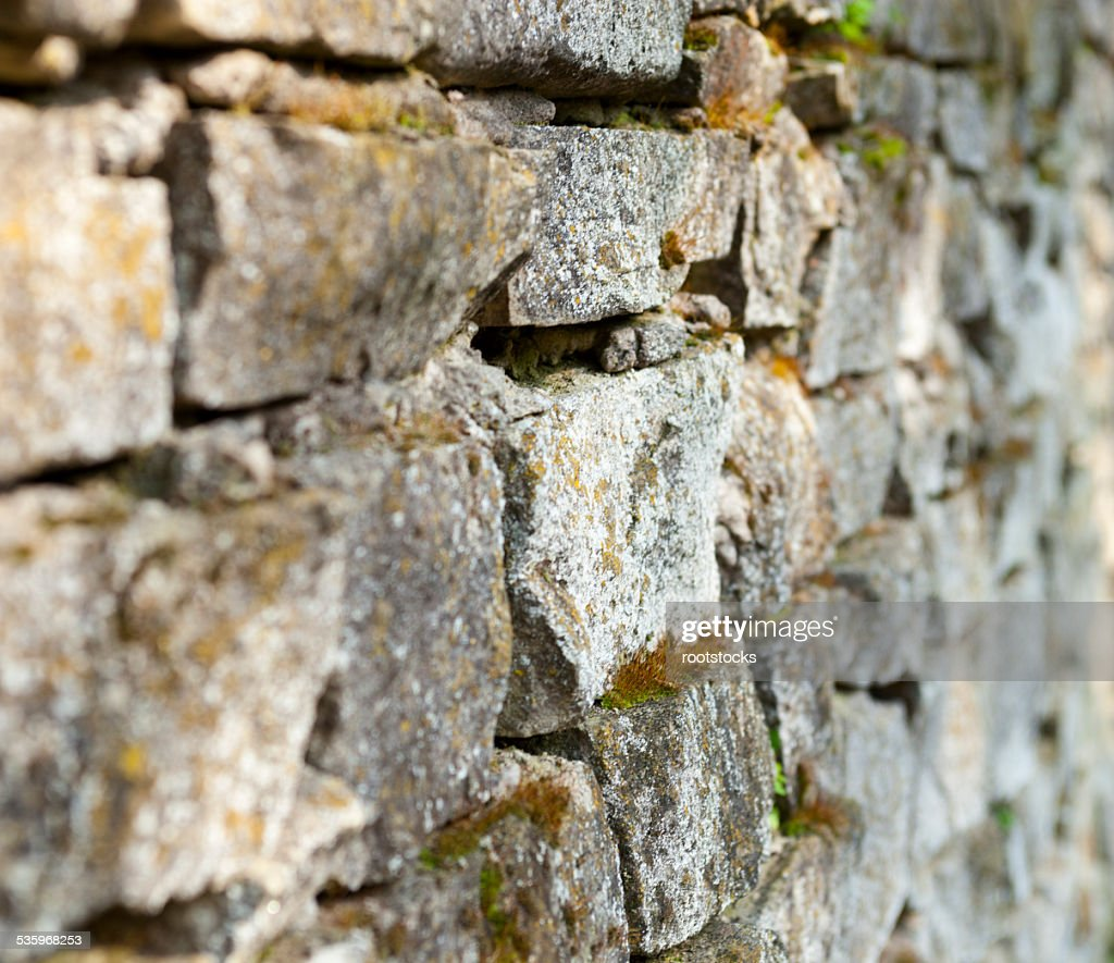 Old stone moss-grown masonry with rich texture : Stock Photo