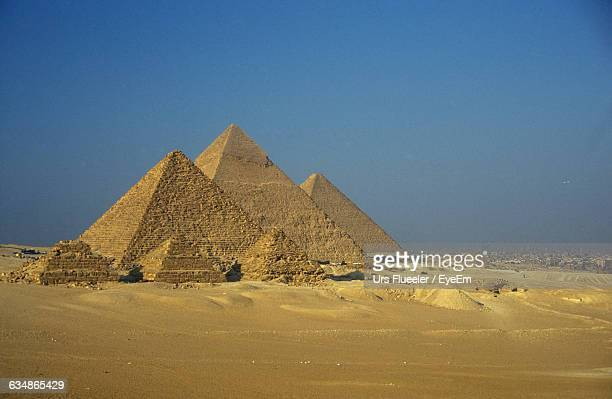 Old Stone Pyramids On Desert Landscape Against Clear Sky