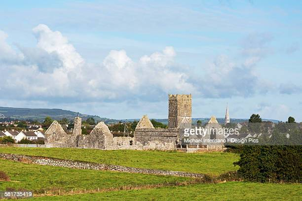 Old stone ruin with church tower and roofless buildings with clouds and blue sky