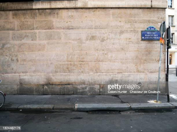 old stone wall and street in the marais in paris - surrounding wall stock pictures, royalty-free photos & images