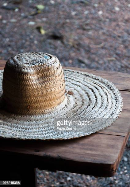 old straw hat on wood bench - straw hat stock pictures, royalty-free photos & images
