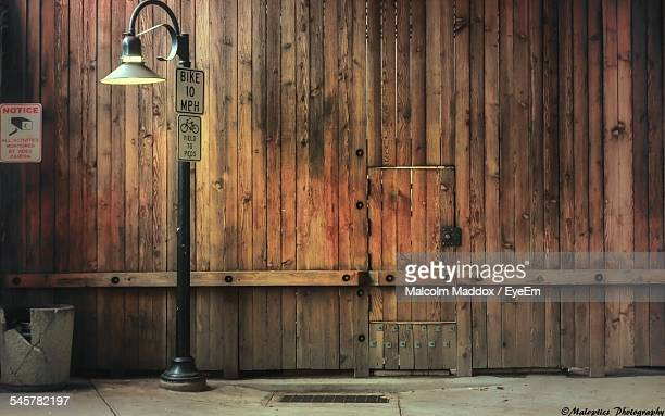 Old Street Light On Sidewalk Against Wooden Wall