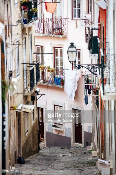 old street with lantern and laundry in alfama district, lisbon, portugal - alfama stock photos and pictures