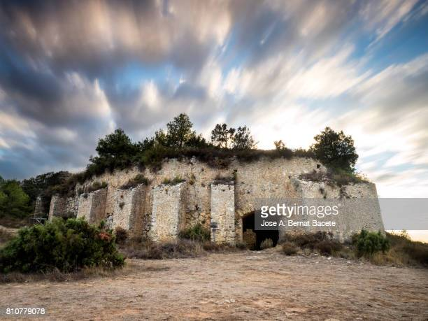 old structure in form of cupula with arches  in the top of a mountain  at dusk with moving clouds, spain. - flying buttress stock photos and pictures