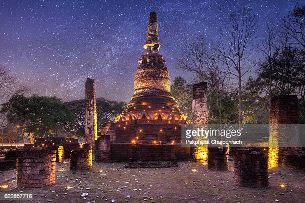 old stupa with candlelight and milky way galaxy in the kamphaeng phet historical park. - sukhothai stockfoto's en -beelden
