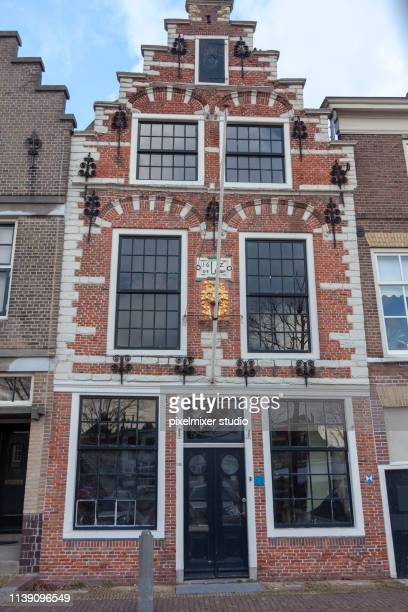 old style building with brown bricks and windows  from white bricks and black painted iron - brille stock pictures, royalty-free photos & images