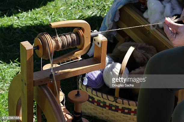 Old style spinning wheel being used to make yarn from lambs wool