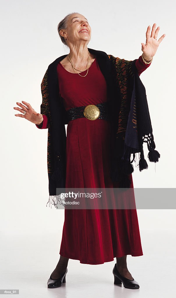 old stylish caucasian gray haired adult female wearing a red dress with a large belt buckle and a colorful shawl  stands posing with her head tilted back and hands raised slightly in a gesture of drama as she her body faces the camera and her gaze is : Foto de stock
