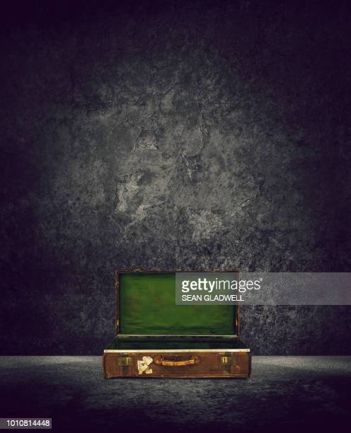 Old suitcase open on ground against wall with peeling plaster