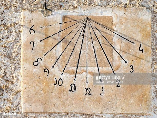 Old sundial in the shade of the correct time