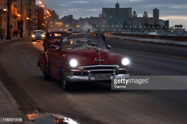 old taxi car driving on the street in havana during the dusk - chevrolet stock pictures, royalty-free photos & images