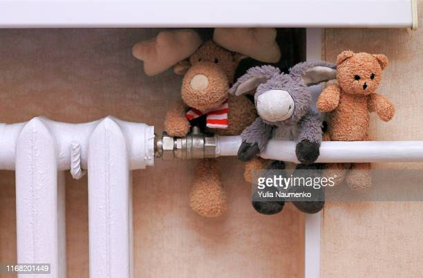 old teddy bear, moose and donkey stuffed toys sitting on white radiator, leaning sadly against a beige wall. the concept of approaching cold weather, low room temperature, cold radiators. - queimadura pele imagens e fotografias de stock