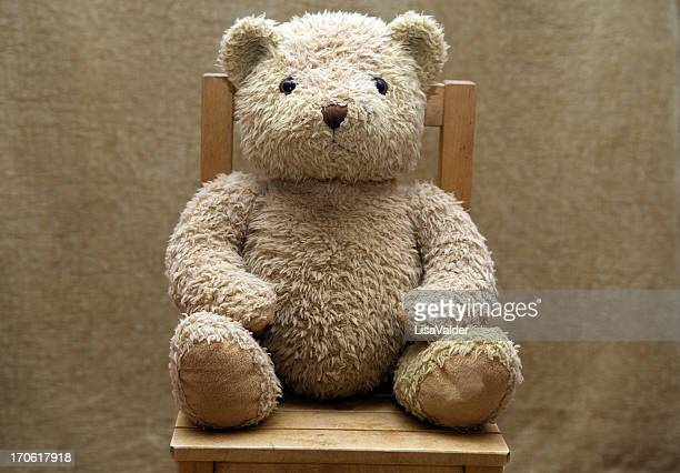 Old teddy bear sitting on wooden chair