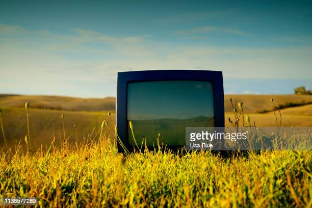 old television abandoned in a field. - obsolete stock pictures, royalty-free photos & images