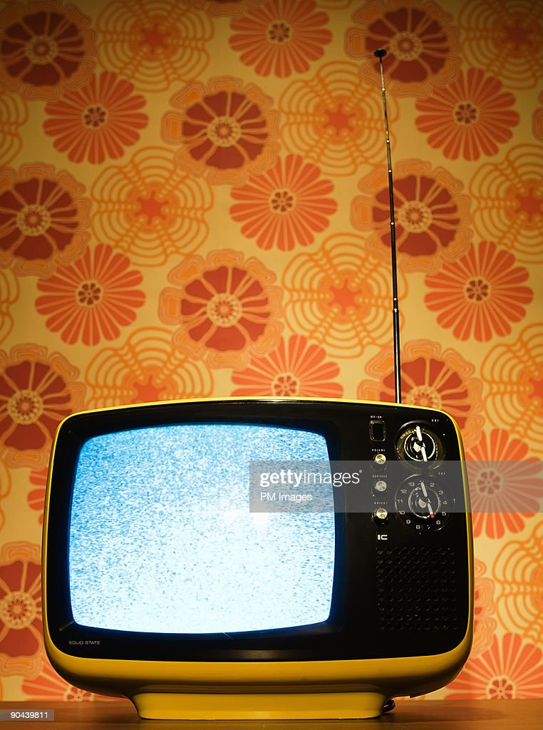 Old Television And Vintage Wallpaper Stock Photo